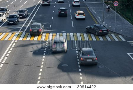 three lanes with a pedestrian crossing, some cars blurred in motion