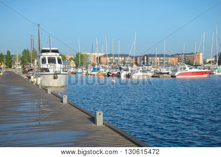 LAPPEENRANTA, FINLAND - AUGUST 09, 2015: August morning on the wooden pier. Yachts and boats standing at the pier in the port of Lappeenranta. Finland