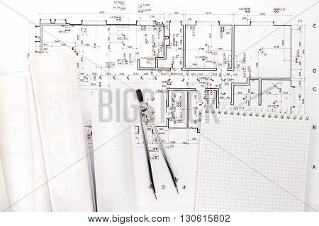 Architectural Blueprint Rolls With Drawing Compass And Notepad