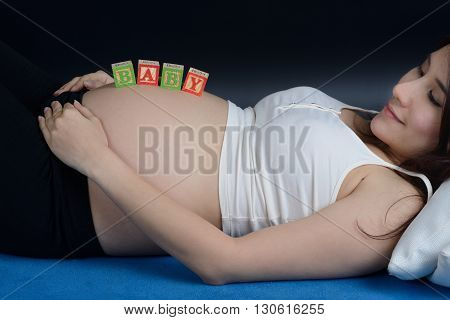Pregnant asian woman put a wooden letter