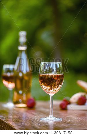Outside setting of wine on a wood table with trees and greenery in the background