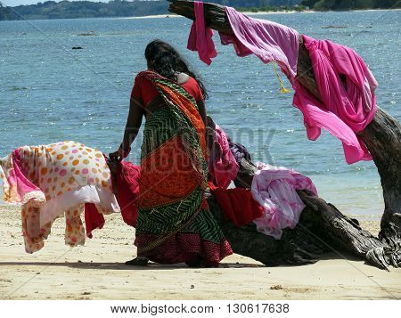 Andaman-Apr 24: A women drying clothes on a driftwood at Wandoor beach, Port Blair Apr 24, 2012 in Andaman and Nicobar Islands, India, Asia.