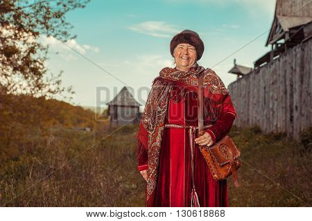 Vintage North Grandmother In Red Dress And Shawl On The Wooden Fortress Background.