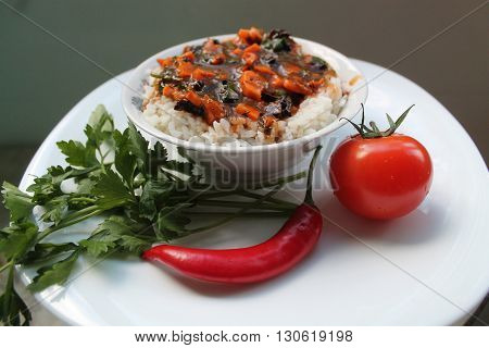 appetizing hot and spicy vegetarian dish from white rice and vegetables sauce with verdure,tomato and chili