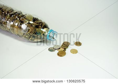 Saving Thai baht coins in recycle bottle isolated on white background