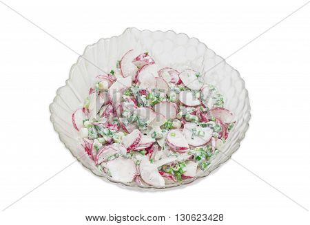Top view to a salad of fresh sliced red radish green onion with sour cream in transparent glass salad bowl on a light background