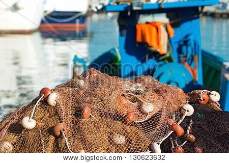 Fishing nets with ropes and floats in the harbor in the background blurred fishing boats