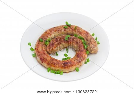 Fried homemade sausage sprinkled with chopped green onions on a white dish