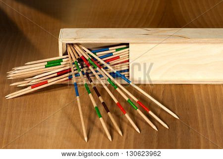Game of mikado or shanghai with wooden sticks and box on a wooden table