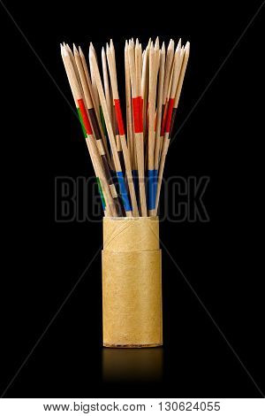 Cylindrical cardboard box with wooden sticks of the Mikado game on a black background with reflections