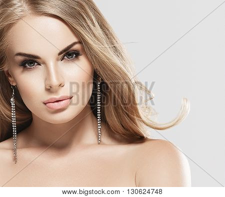 Woman With Blonde Hair. Studio Shot. Gray Background.