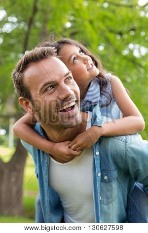 Father giving a piggyback ride to his daughter outdoors