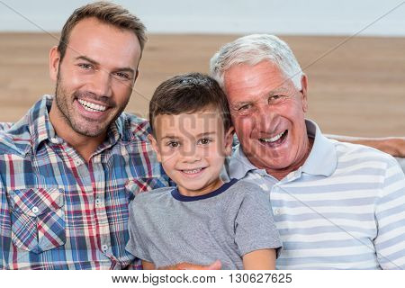 Father, son and grandson sitting on sofa and smiling in living room