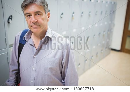Portrait of professor standing in locker room in university