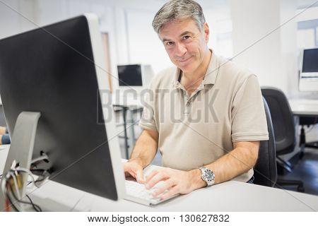 Portrait of happy professor working on computer in classroom