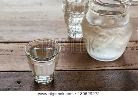 Glass of water and pitcher glass on wooden table background.