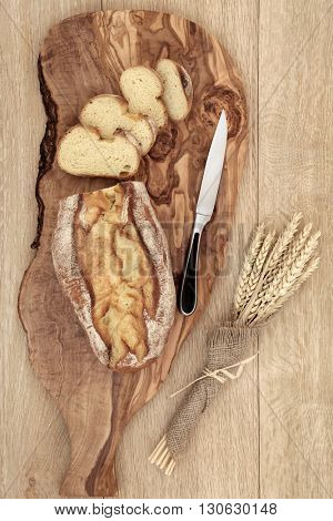 Rustic homemade bread loaf with slices on an olive wood board with knife and wheat sheaths in hessian  over oak wood background.