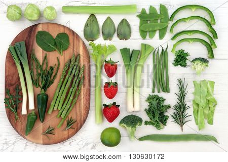 Red and green fresh super food with vegetable and fruit selection over distressed white wood background. High in vitamins, antioxidants, minerals and anthocyanins.