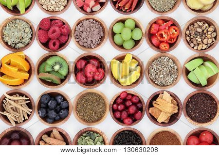 Food selection for cold and flu remedy to boost immune system, high in vitamins, anthocyanins, antioxidants and minerals in wooden bowls over white background.