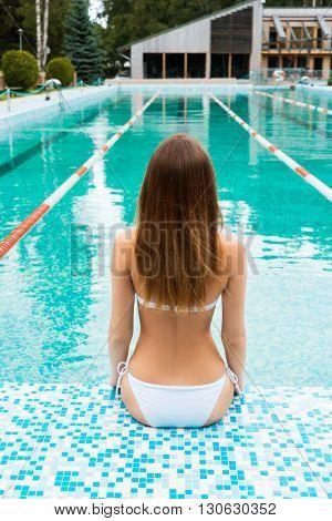 The back view of beautiful woman in white bikini sitting on a pool tile.