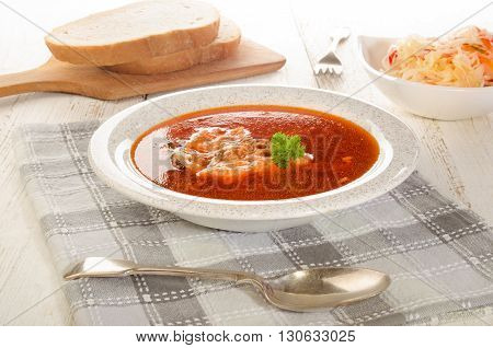 hungarian fish soup in a soup plate salad and bread on a wooden board