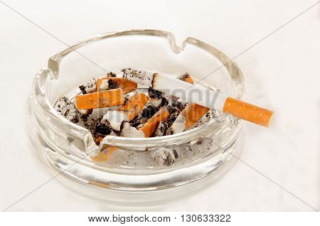 ashtray with cigarette and ash on light background