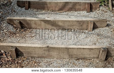 Makeshift stairs to the forest path made of planks and filled with gravel