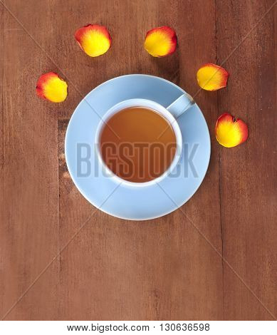 A teal blue cup of tea with rose petals around it shot from above on a dark brown wooden texture with copyspace