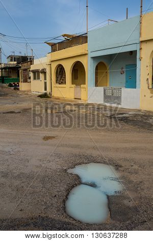Small colorful weekend houses at the banks of Mediterranean sea. Road with paddles after a night rain. Blue sky.