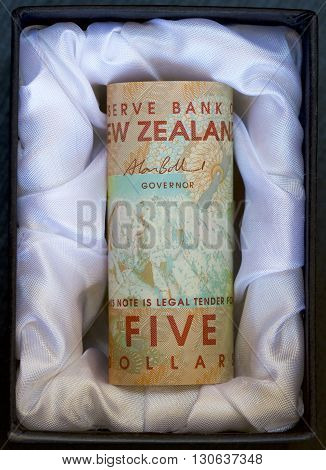 New Zealand dollar notes in a silk lined coffin.