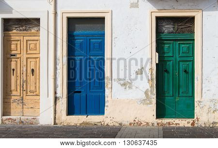 In the rays of morning sunlight 3 similar doors different in the color. House at the island Malta Europe.