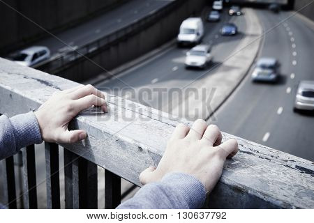 Depressed Young Man Contemplating Suicide On Road Bridge