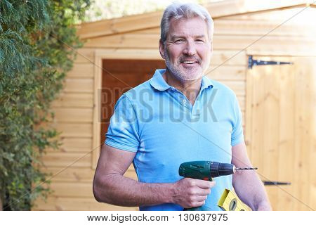Handyman Standing Outside Garden Shed With Tools