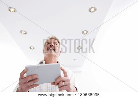 Man Controlling Lighting With App On Digital Tablet