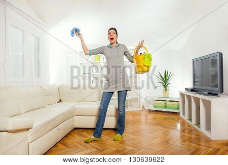Funny woman mopping floor and singing in the living room