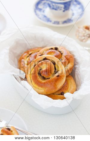 Fresh baked vanilla sweet sugar buns with chocolate drops in a bowl on a kitchen background