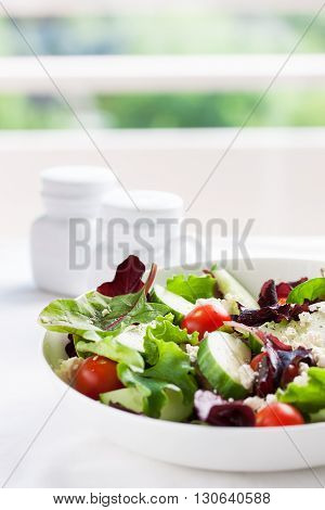 Summer season salad with salad leaves tomatoes cucumbers Italian herbs and cheese in a bowl on a table with copy space closeup selective focus