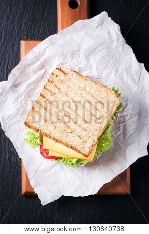 Toasted sandwich with salad leaves tomatoes and cheese with fork on a cutting board on a dark background top view