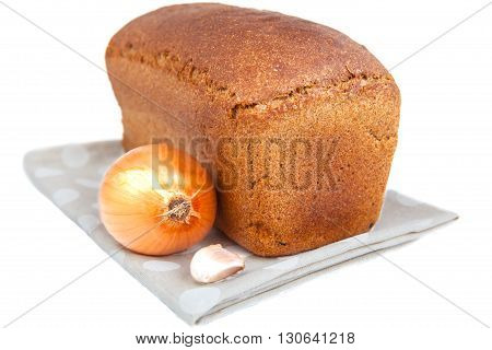 Loaf of bread onion and garlic clove on doily isolated on white