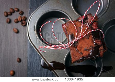 Homemade chocolate sweet coffee brownies cakes with chocolate sauce or syrup on a dark background horizontal with place for text