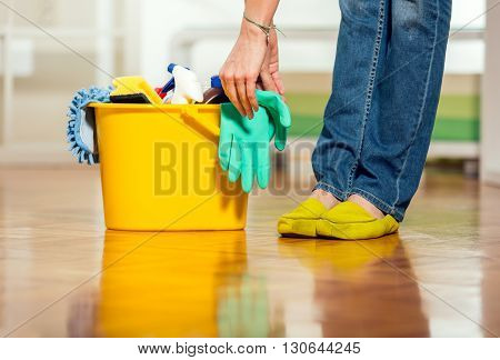 Female legs beside bucket with cleanser in the living room