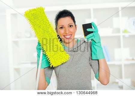Woman in protective gloves holding a sponge and mop for cleaning