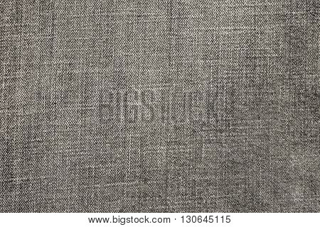 the textured background from rough cotton material or denim of pale beige color