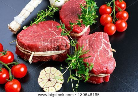 Fresh Raw Beef steak Mignon, with salt, peppercorns, thyme, tomatoes. Ready to cook