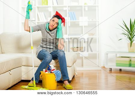 Woman with cleaning supplies sitting on the couch