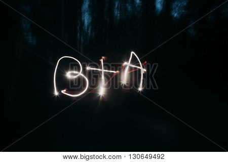 Light painting of initials on night background.