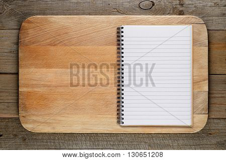 Chopping board and cookbook on wooden background