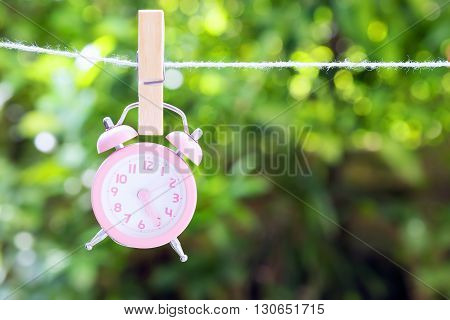 the pink analog alarm clock hanging on the rope