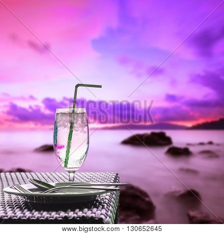 Glass of cold water on dining table with lone exposure fancy colorful seascape sunset background