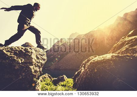 Man running on Mountains jumping cliff over lake Skyrunning sport Lifestyle Travel concept outdoor